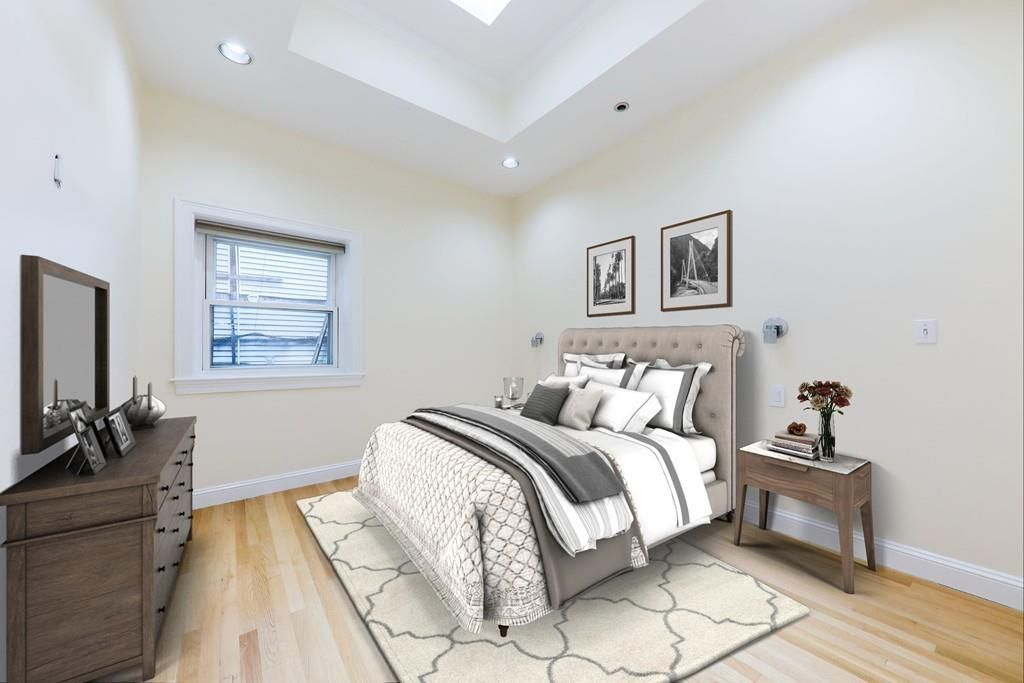A bedroom with a bed facing a dresser with a TV mounted above it.
