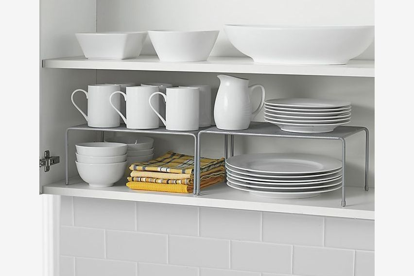 Two shelves inside a cabinet with a set of white ceramic dishes