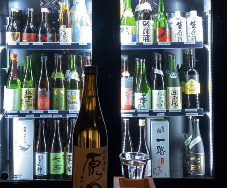 A fridge displaying bottles of sake, with a bottle and shot glass in the foreground