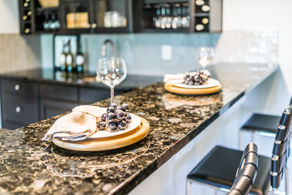 Two place arrangements on a kitchen counter, with wine glasses and fake grape bunches at each.