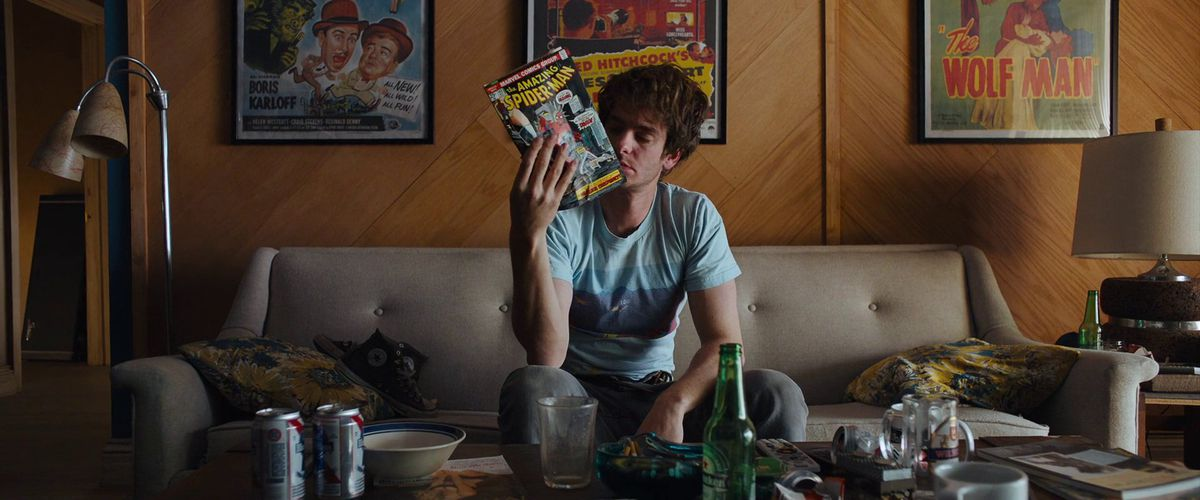 Andrew Garfield as Sam in Under The Silver Lake holds up a Spider-Man comic, in a room lined with posters for classic Hollywood films.