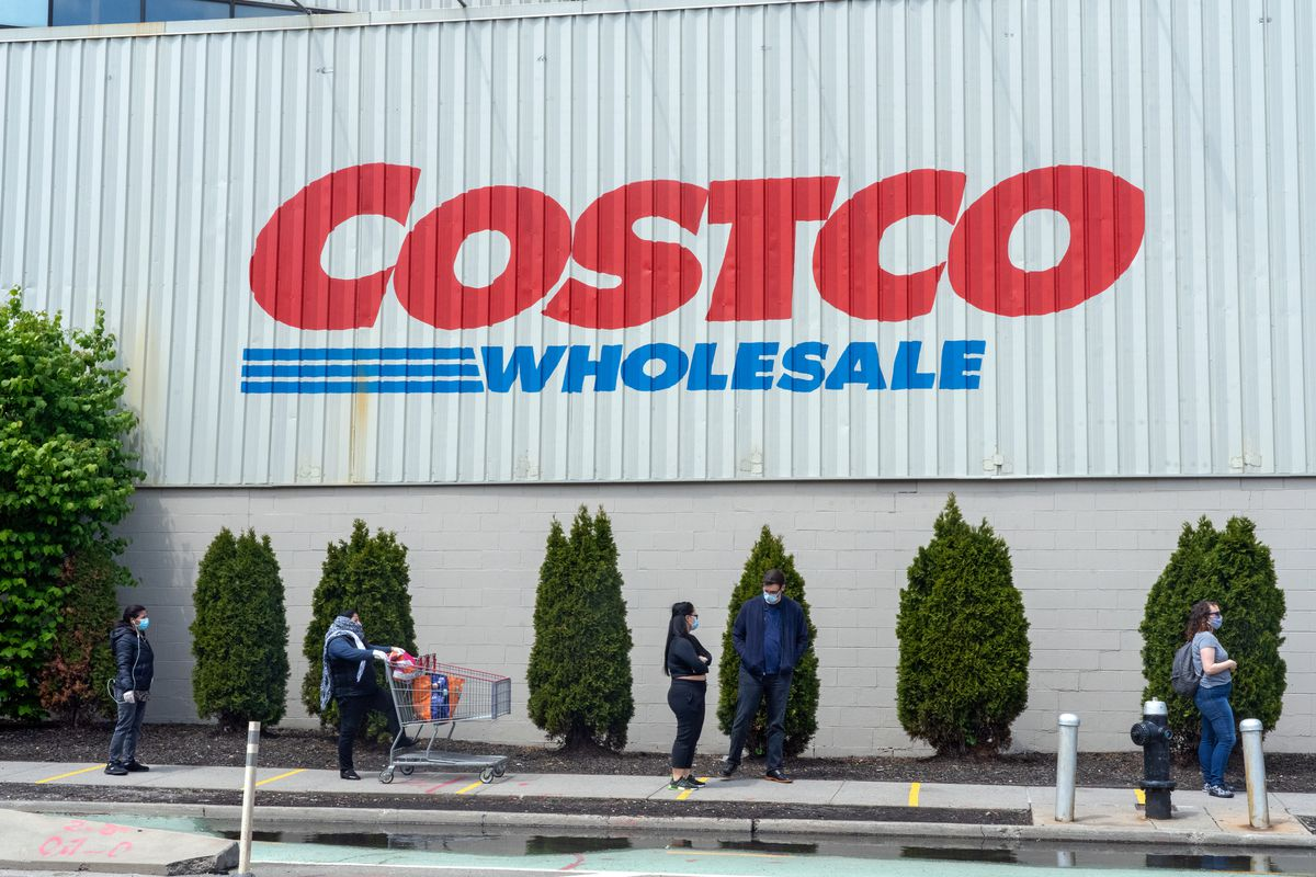 Shoppers wearing masks line up outside a Costco Wholesale warehouse, spaced out for social distancing.