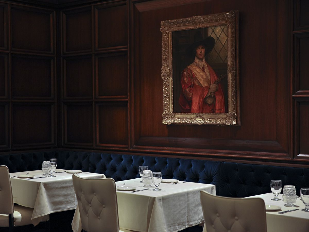 A line of white tablecloth tables in front of an oil painting of a regal looking guy