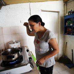 Ruby C. Rosales cooks food in Cebu, Saturday, Nov. 23, 2013. The Rosales family was displaced from Tacloban to the home of a friend in Cebu following a typhoon.