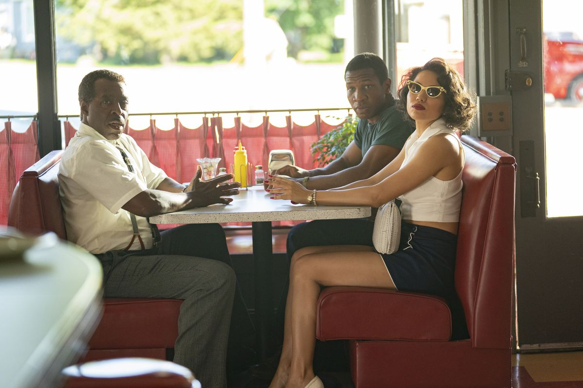 Jonathan Majors, Courtney B. Vance, and Jurnee Smollett sit in a booth in a diner in HBO's Lovecraft Country.