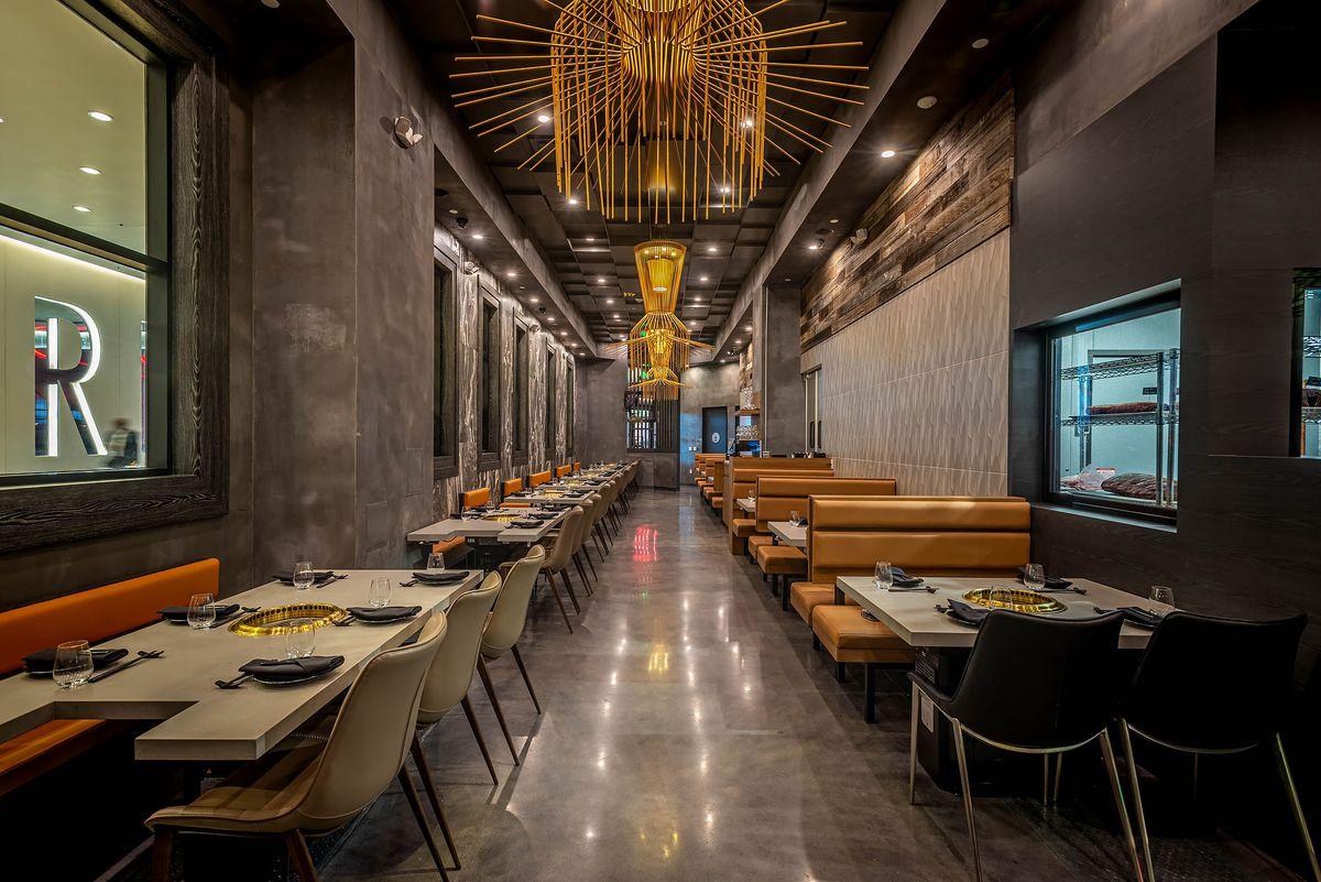 AB Steak interior with sleek dining room, striking chandelier lights.
