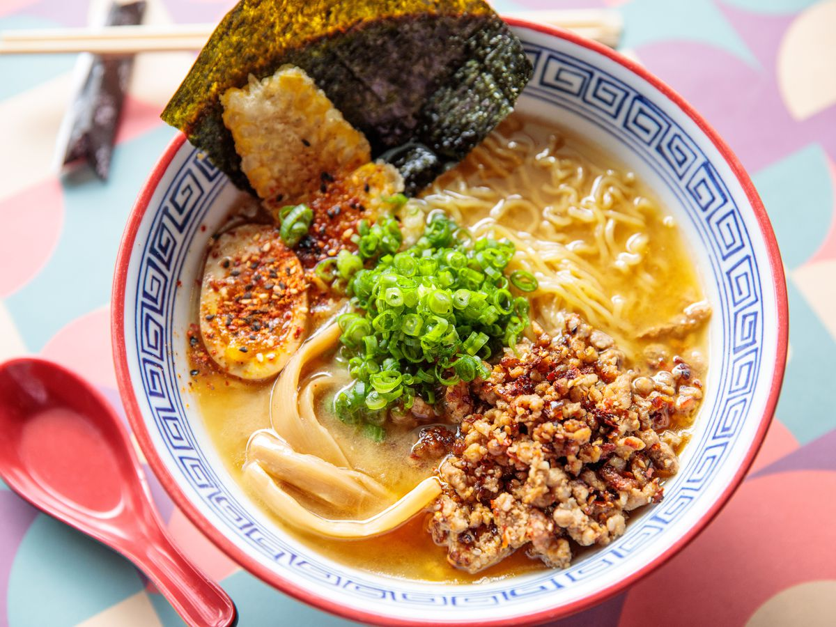 A colorful bowl filled with ramen broth, noodles, a soft egg, and toppings with a pink spook alongside it