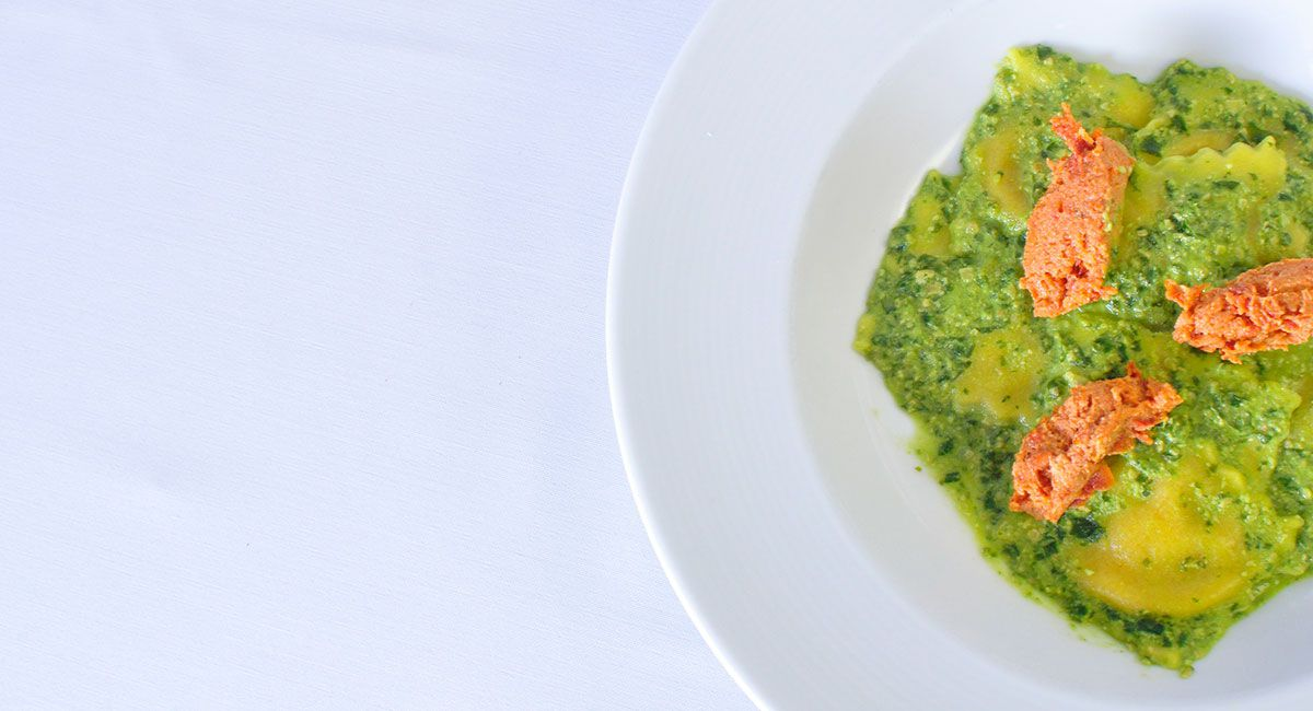 Overhead view of a white dish of ravioli covered in a green pesto and garnished with dollops of a thick, orange paste