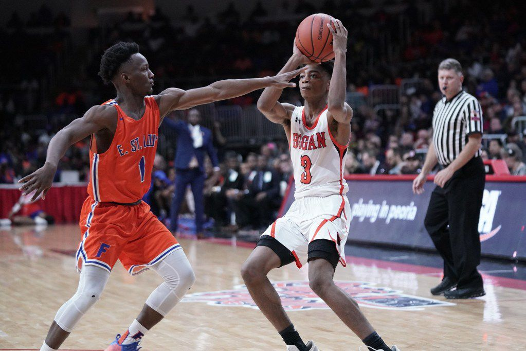 Bogan's Antione Bloxton (3) moves the ball out of reach of East St. Louis' Jashawn Anderson (1) in the 3A state championship game.