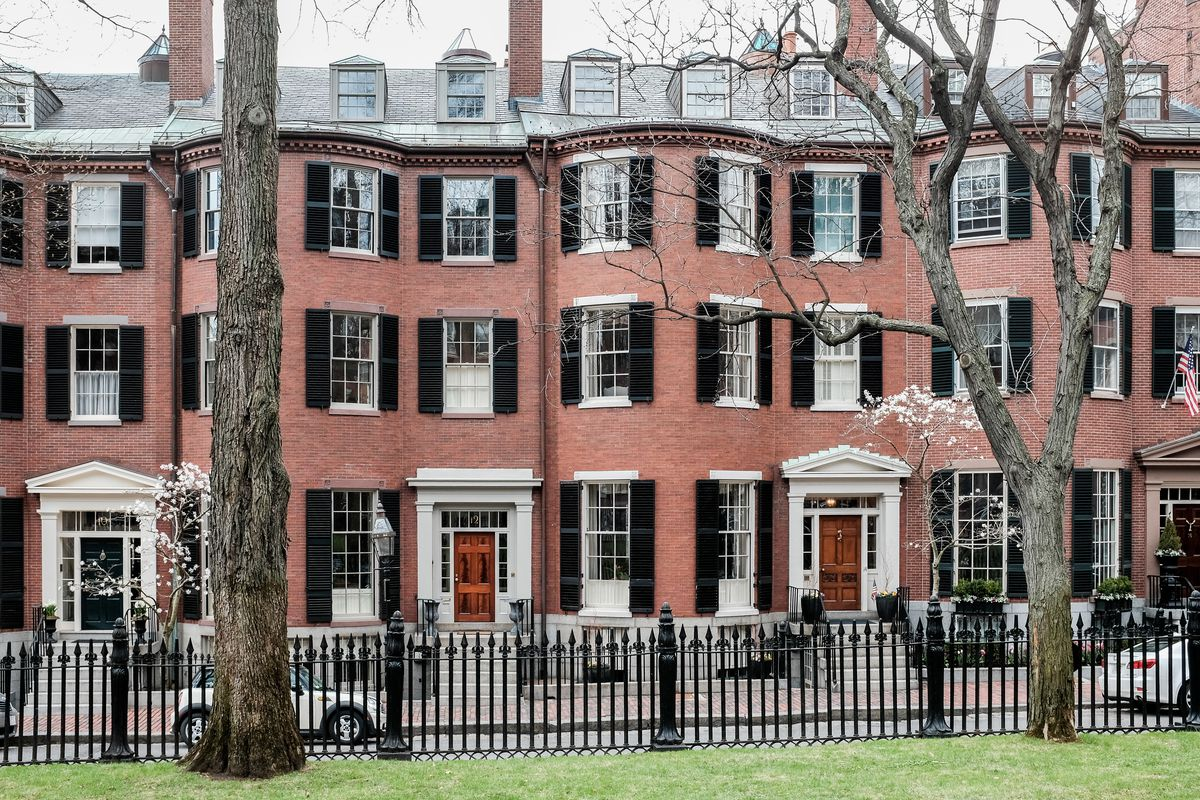 Greek revival townhouses along a garden with a black wrought-iron fence.