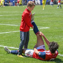 The ball boy helping stretch Johan Gomez (9) during the opening match of the 40th Annual Dallas Cup.