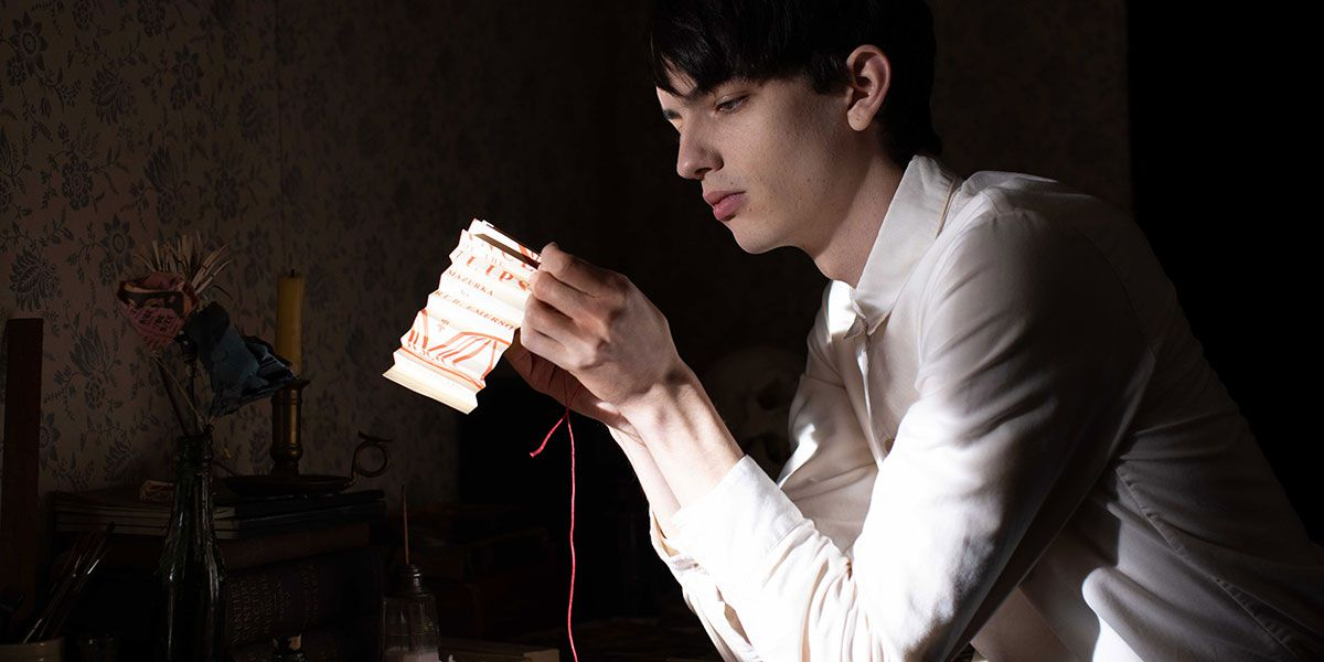 Kodi Smit-McPhee sews red thread through a white cloth in a darkened room in The Power of the Dog