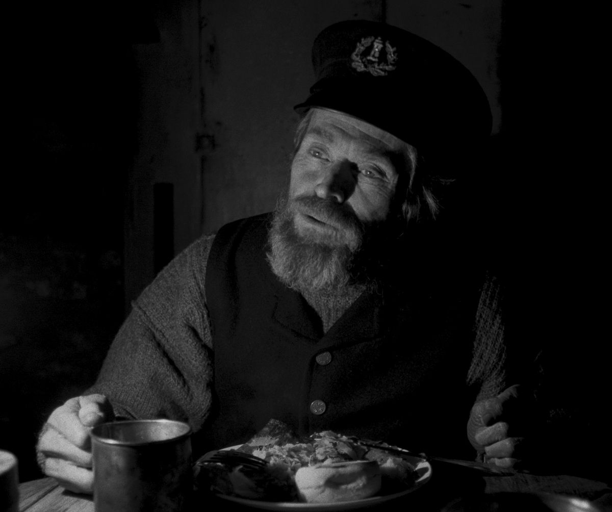 Thomas (Dafoe) speaks over a plate of food and a cup.