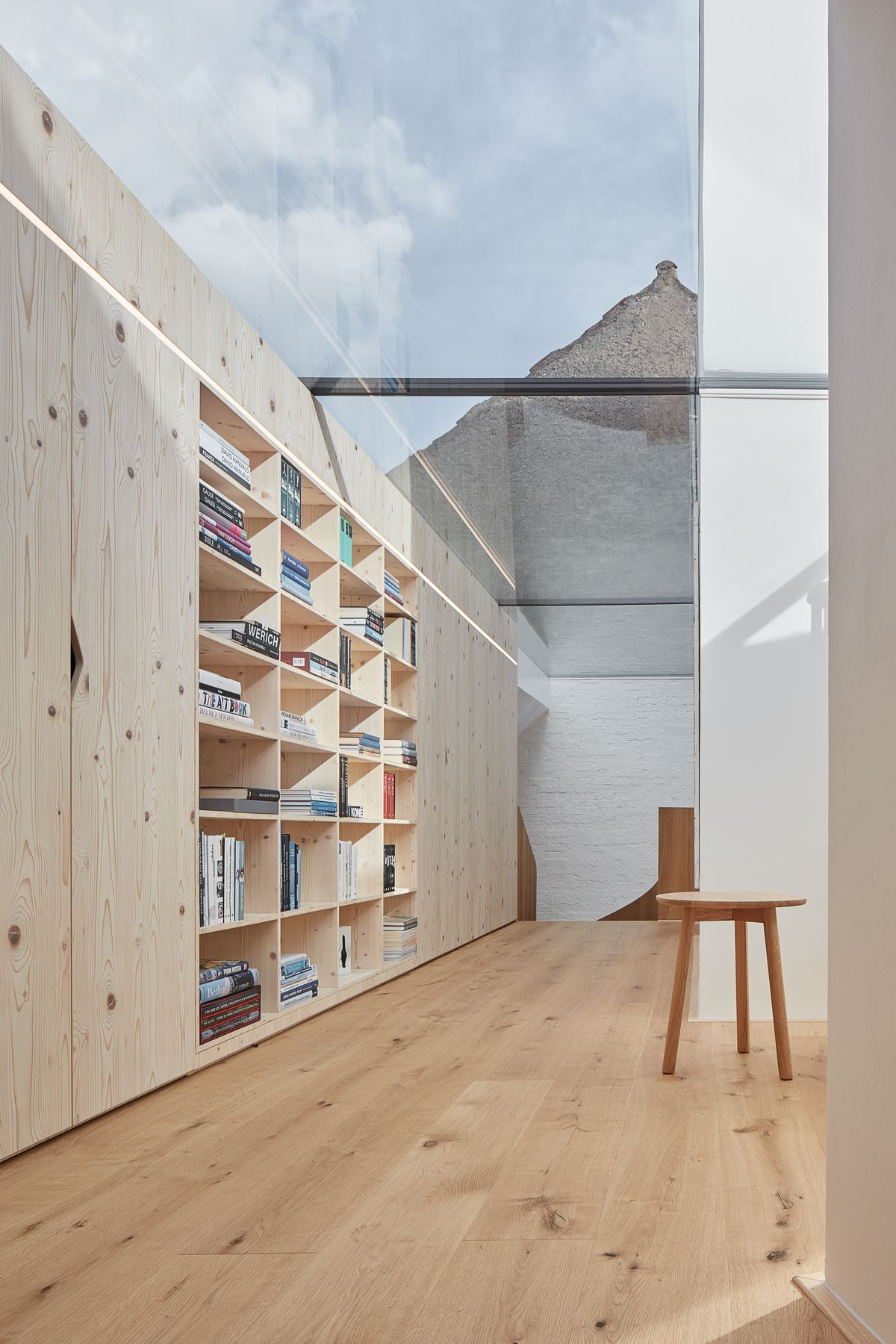 Room with built-in bookshelves and a ceiling made of glass.
