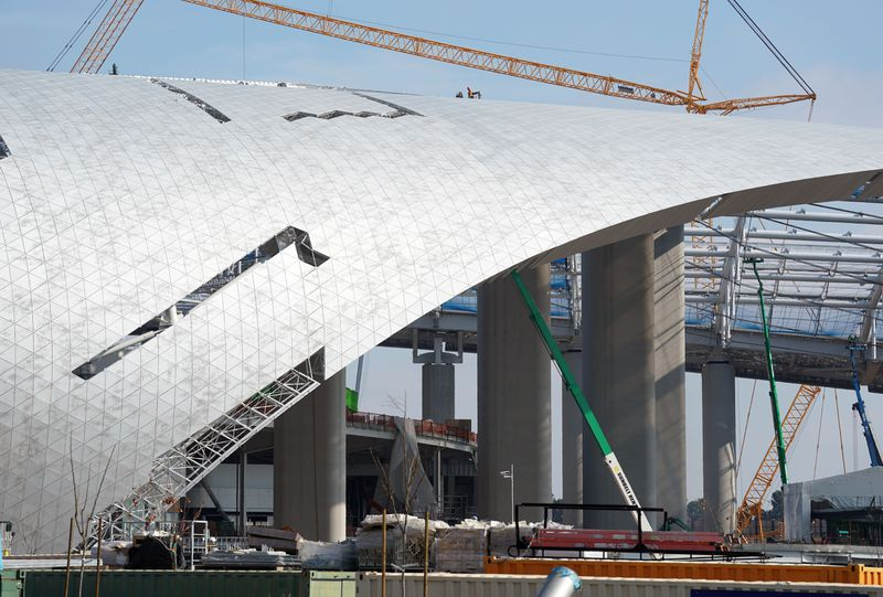 The clear plastic panels that will make up the roof of the stadium are being put into place. Some gaps are visible, showing that work is still in progress.
