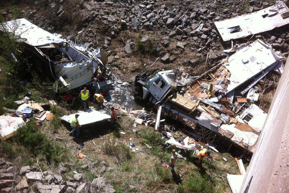 Officials work the scene of a Minnesota-bound motor home on Sunday, April 1, 2012 in a ravine off Interstate 35 in northeast Kansas. The Kansas Highway Patrol said the northbound Freightliner motor home was carrying 18 people and pulling a trailer when th