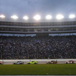 Cars pass under the lights during the NASCAR Sprint Cup Series auto race at Texas Motor Speedway Saturday, April 14, 2012, in Fort Worth, Texas.