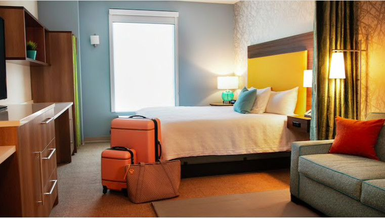 A hotel room with a bed and luggage next to it.