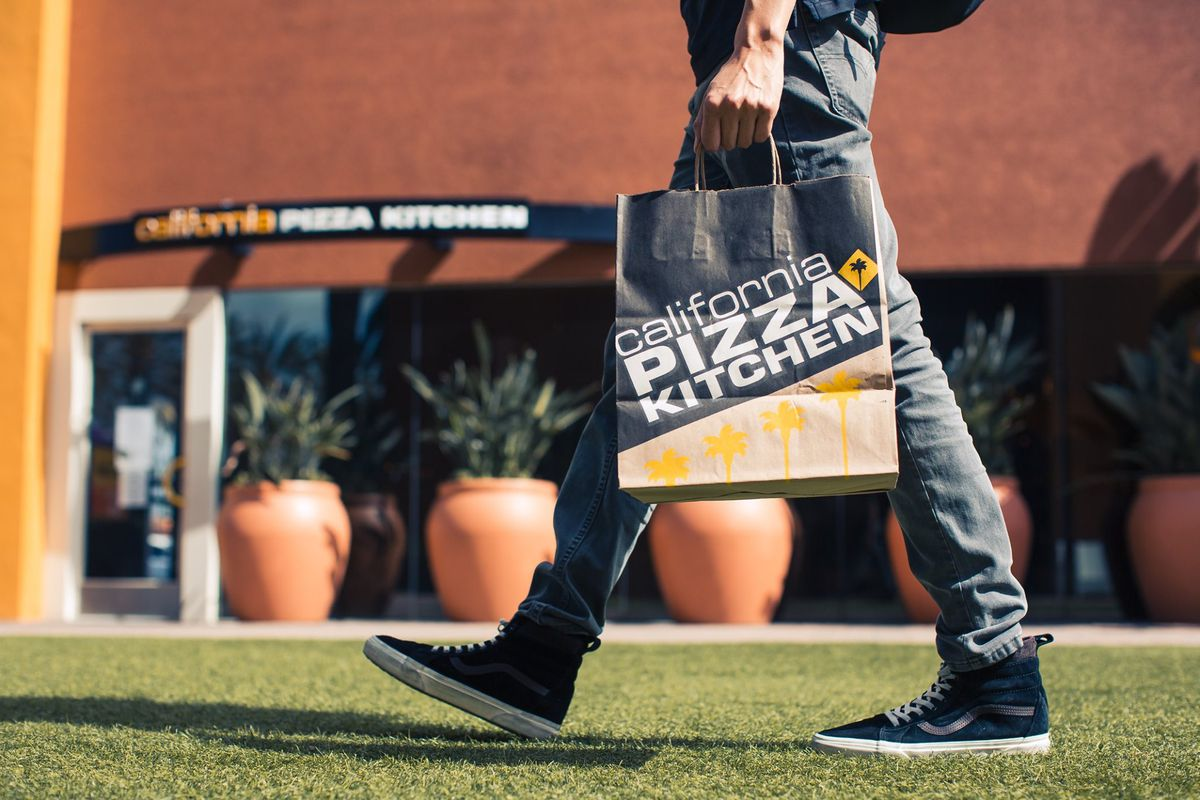 A man carries a bag holding CPK food in front of the restaurant.