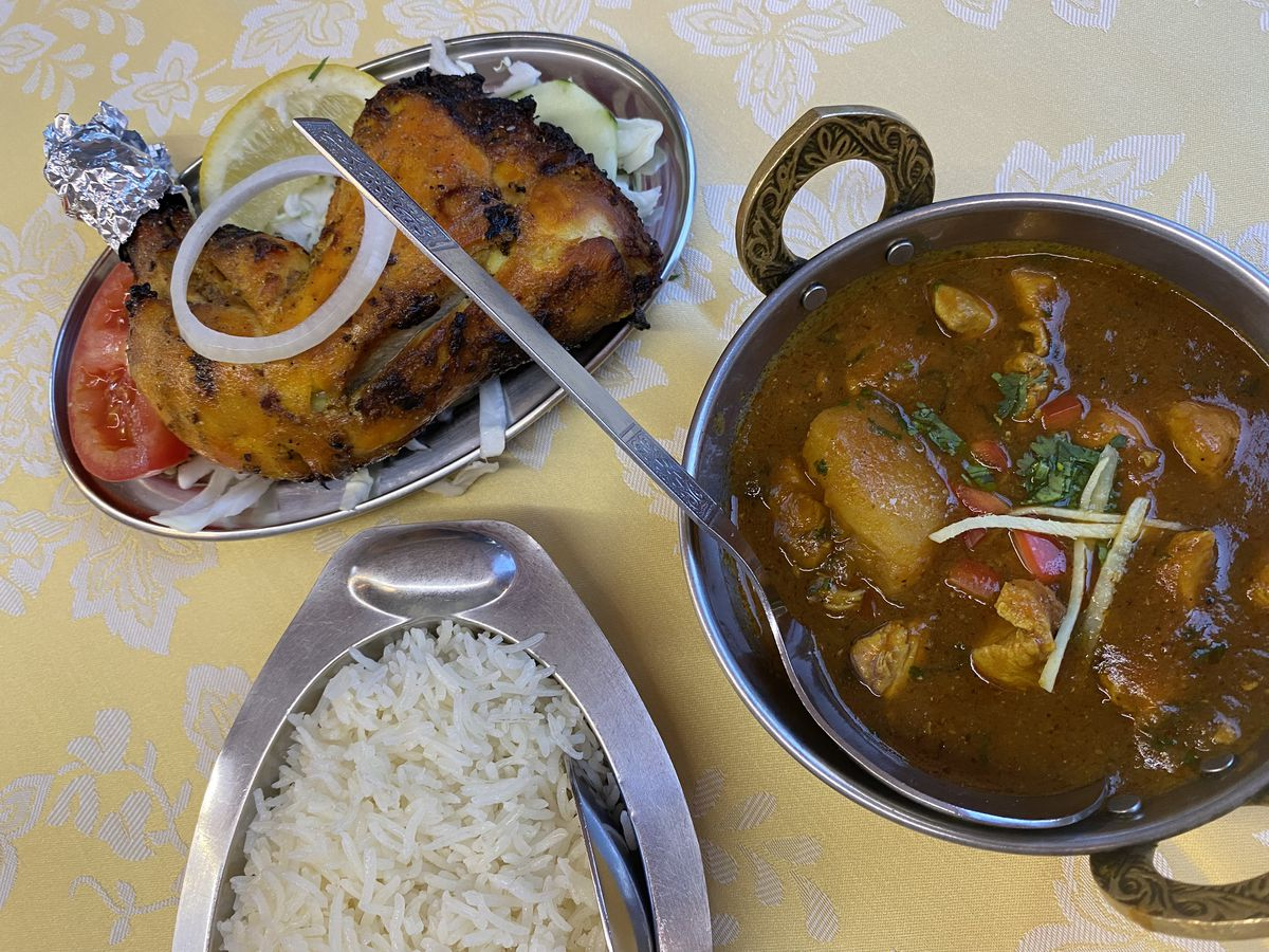 A table set with a decorative table cloth. On top are a large stew pot of chicken vindaloo, a bowl of white rice, and a dish of tandoori chicken