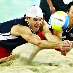 Jake Gibb, left, and Sean Rosenthal, right, dive to return the ball to Brazil's team in their men's quarterfinal beach volleyball match duringthe 2008 Beijing Olympic Games. Brazil won 2-0. Gibb is headed back to the Olympics in London.