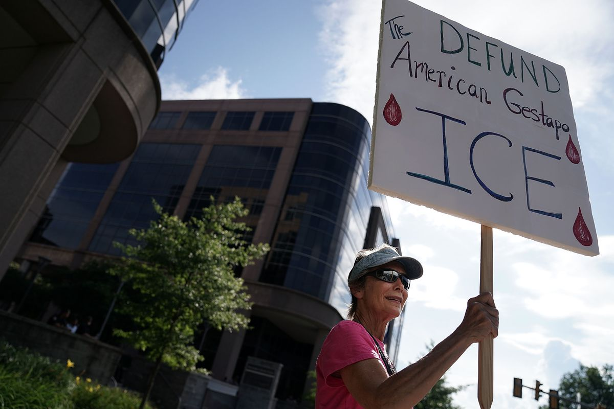 An activist holds a sign during a protest to abolish ICE.