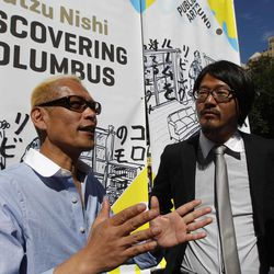 """Japanese artist Tatzu Nishi, left, speaks to reporters with the help of translator Kasuke Fujitaka during a media preview of """"Discovering Columbus,""""  Wednesday, Sept. 19, 2012 in New York.  The 810-square-foot living room offers spectacular views of mid-Manhattan. A 13-foot statue of Christopher Columbus stands amid the couches, lamps and coffee table."""