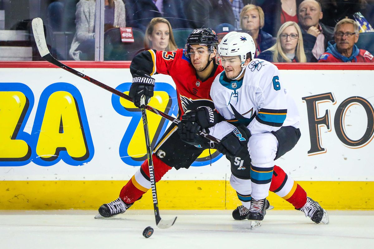 Sep 25, 2018; Calgary, Alberta, CAN; Calgary Flames left wing Johnny Gaudreau (13) and San Jose Sharks defenseman Ryan Merkley (6) battle for the puck during the first period at Scotiabank Saddledome.