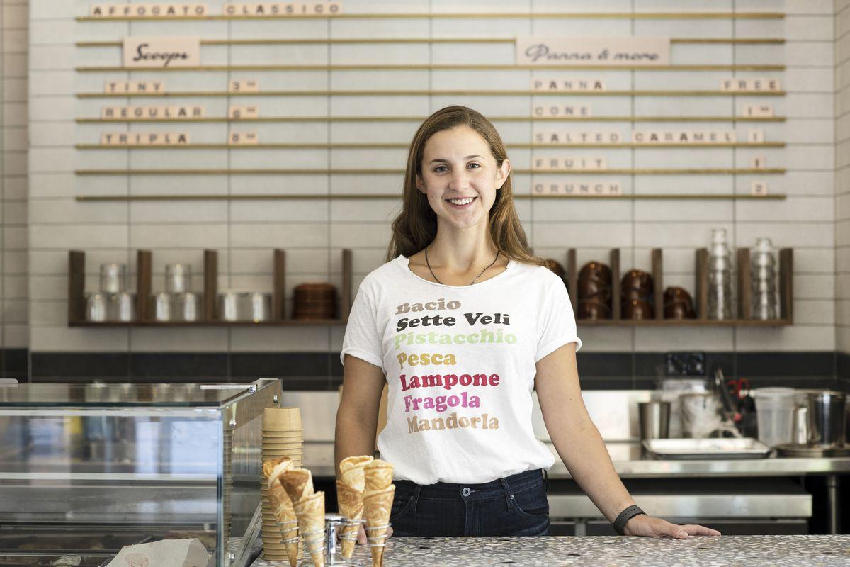 A woman standing behind an ice cream bar wearing a white shirt