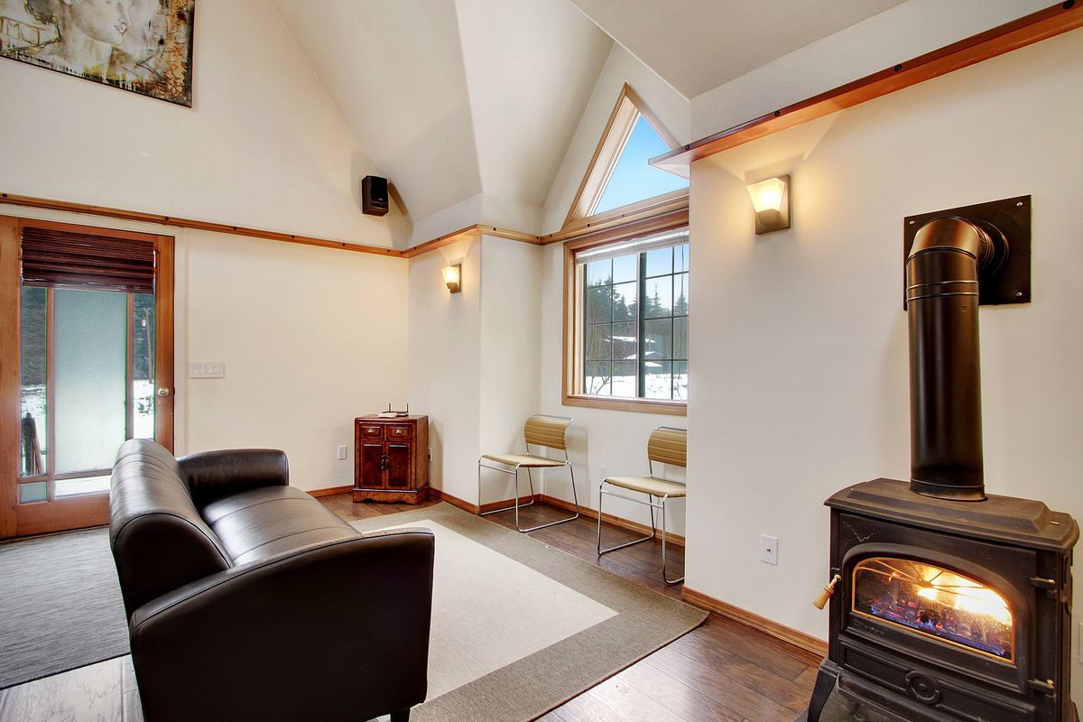 A small cottage living room with a wood stove, vaulted ceilings, and a peaked window
