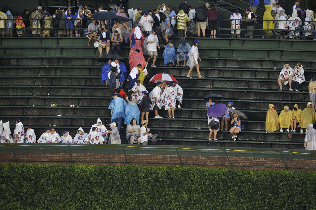 Fans leave the ballpark as the game between the Washington Nationals and the Chicago Cubs has been postponed because of rain at Wrigley Field in Chicago, Illinois.  (Photo by David Banks/Getty Images)