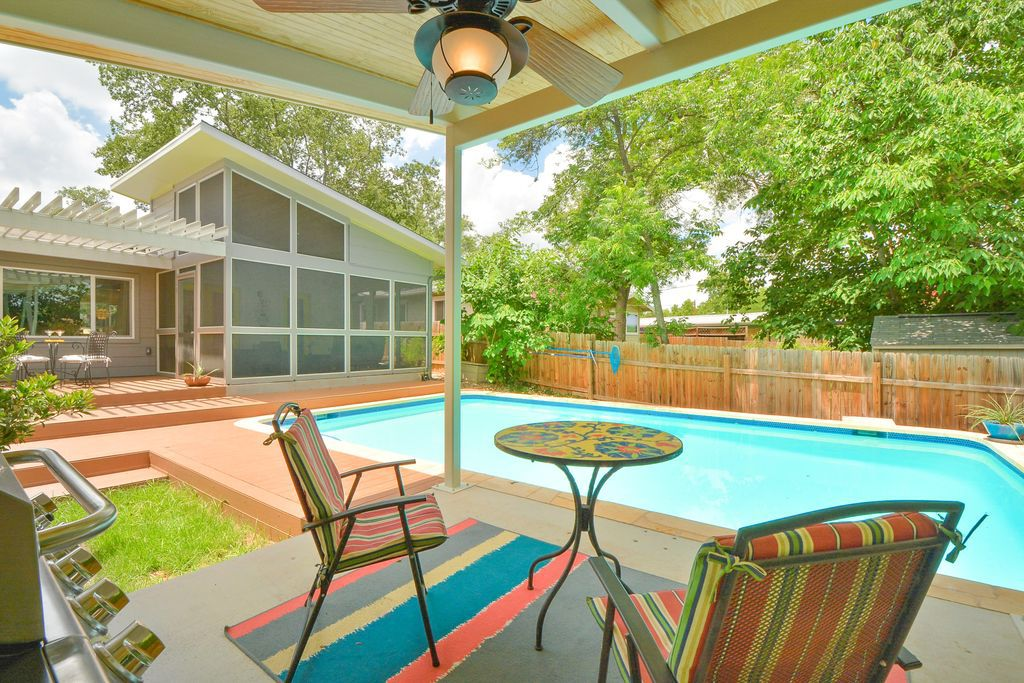 A swimming pool with a lounge area that has chairs and a table. The pool is adjacent to a house with multiple windows.