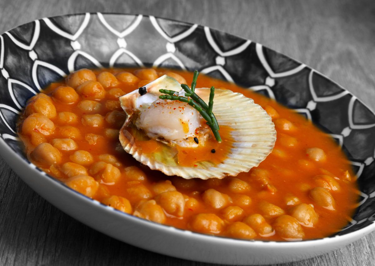 A bowl with a single scallop in its shell floating atop a bed of chickpeas and stew.