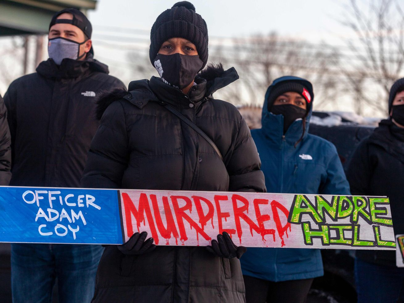 A demonstrator holds a sign condemning Officer Adam Coy at a press conference and candlelight vigil for Andre Hill in Columbus, Ohio on December 26, 2020.