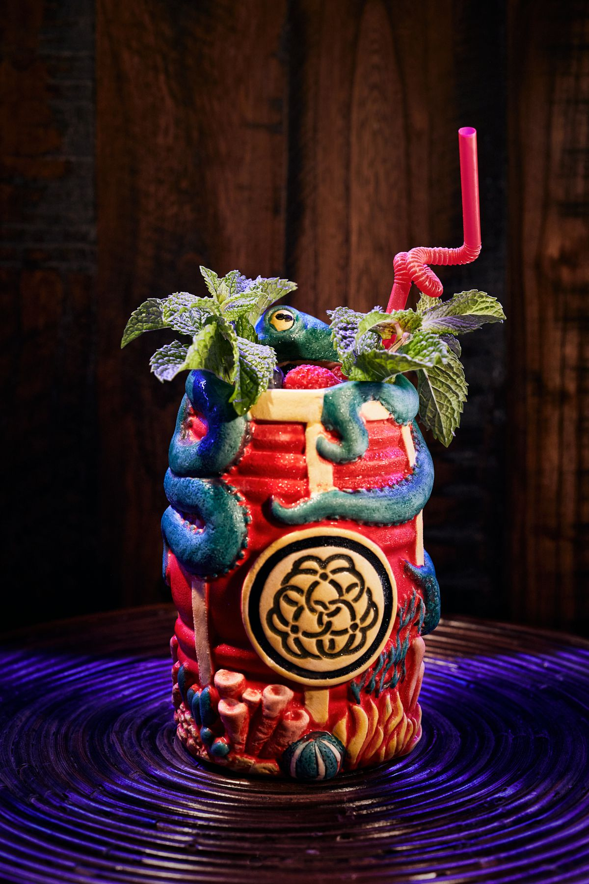 A tiki mug of a red barrel with a black-and-white insignia with a blue octopus hugging it
