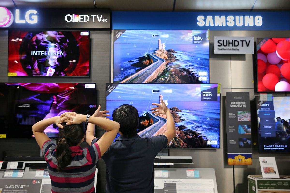 Two people standing in front of a display of flat-screen TVs in a big-box store.