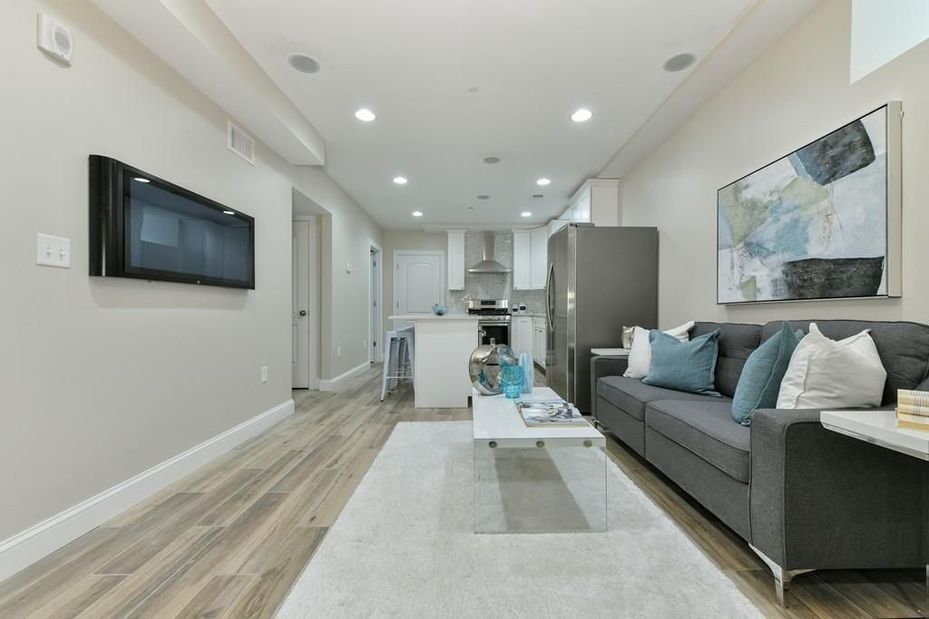 A long, narrow living room leading to an open kitchen.