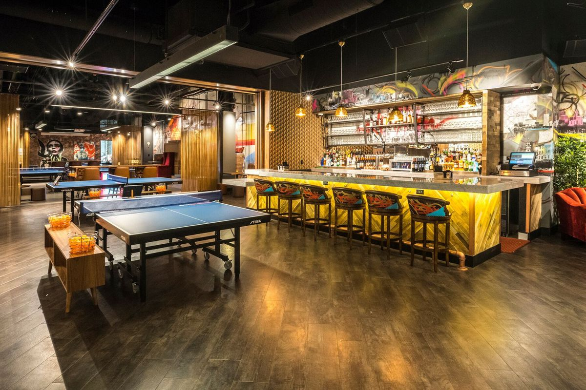 a big room with a ping pong table and a bar