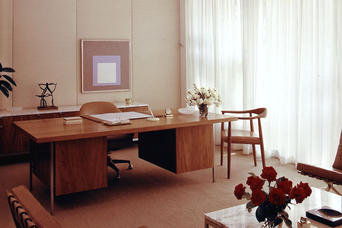 An archival image of an office with a large table and artwork hanging in the back wall.