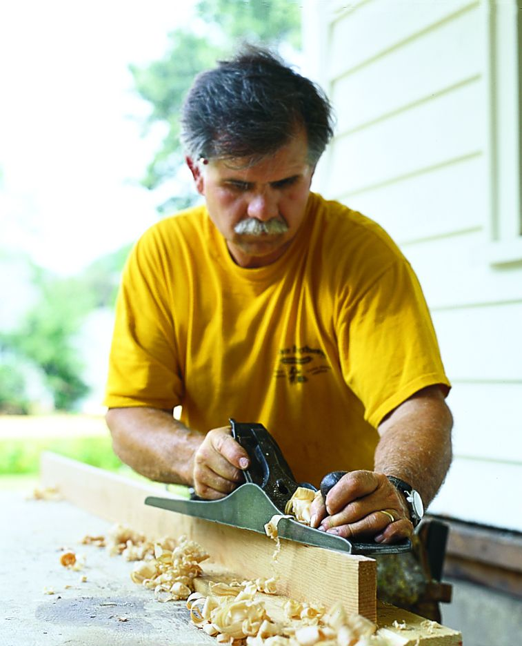 Person using a hand plane tool on wood.