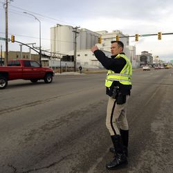 A police officer directs traffic on 500 South in Salt Lake City after traffic lights went out following a 5.7 magnitude earthquake centered in Magna hit early on Wednesday, March 18, 2020.