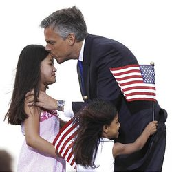 Jon Huntsman Jr. kisses one of his daughters while his other daughter rushes him after the announcement. Huntsman wil be in Utah next week for fundraising and possibly a rally.