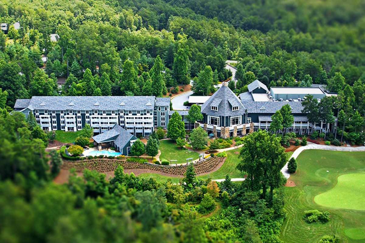 An aerial view of a large resort building surrounded by trees and grass.