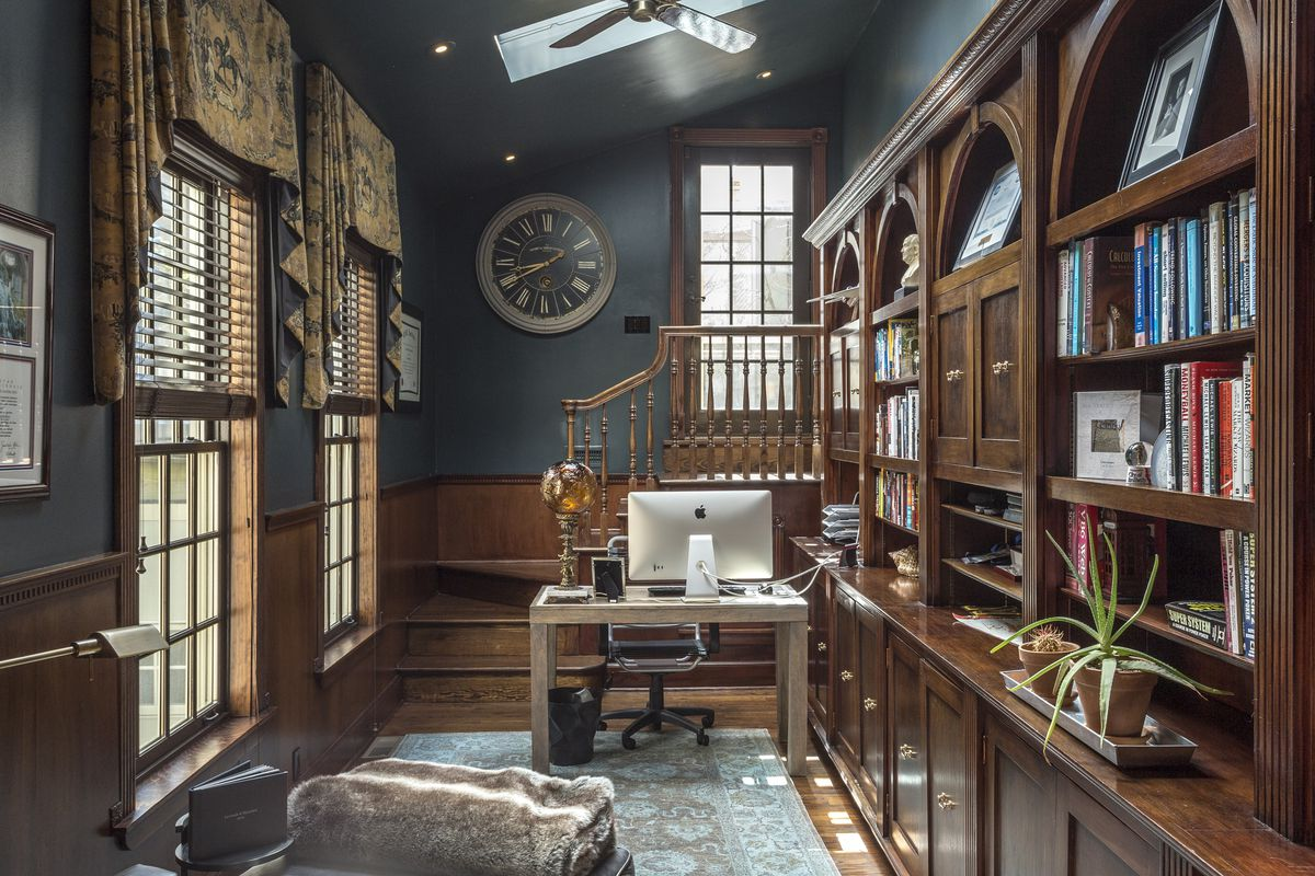 A library with vaulted ceilings and rich, dark wood built-ins.