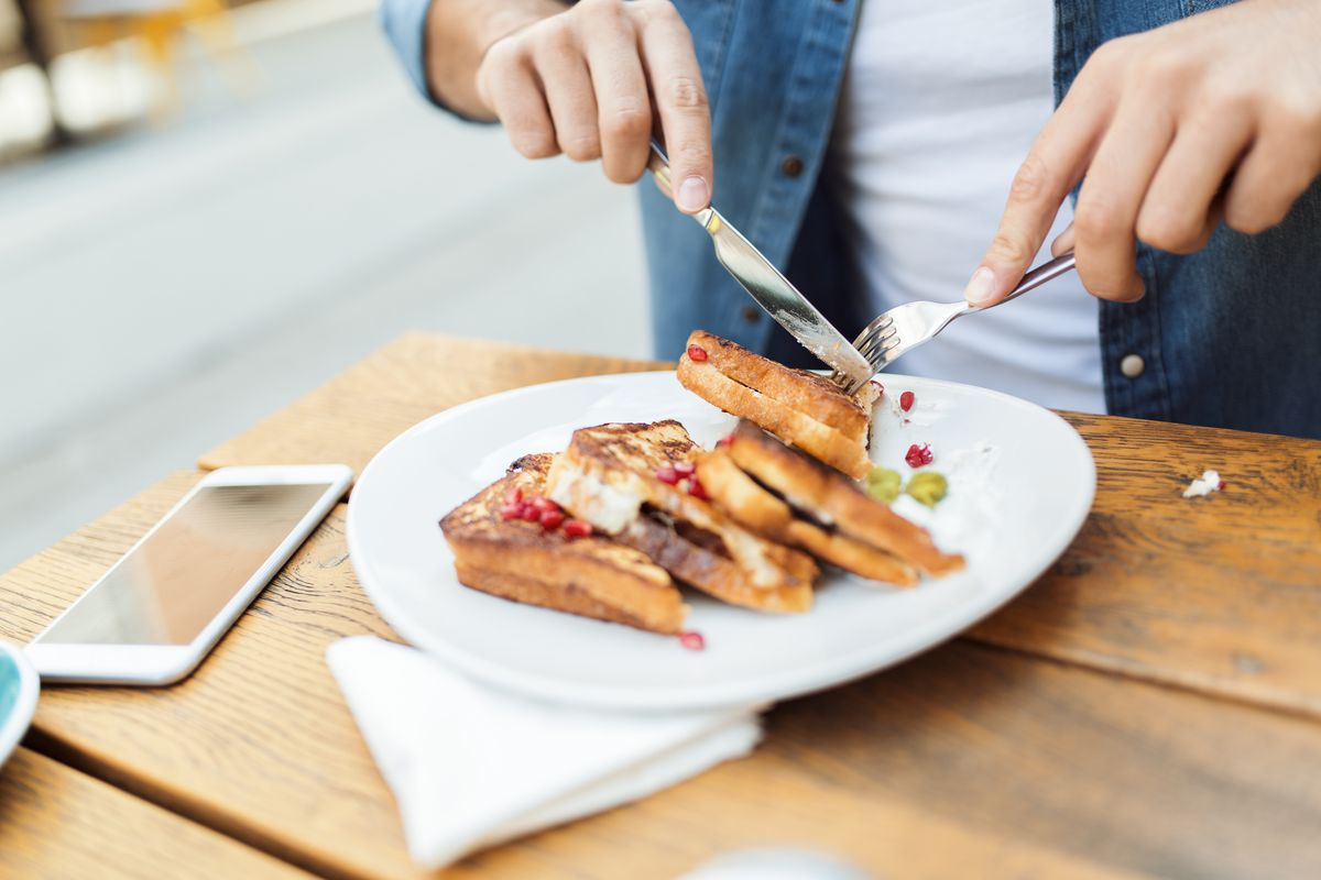 Hands using fork and knife to eat sandwiches or french toast on a plate.