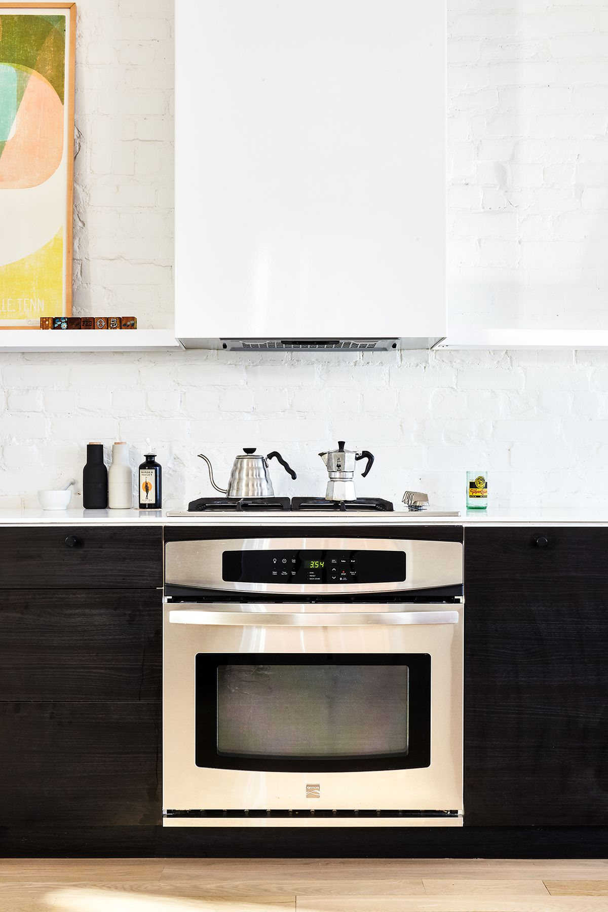 A kitchen with black cabinetry and white exposed brick walls. There is an oven and on the stove are a kettle and coffee maker.