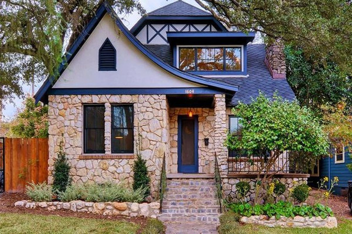 Alsatian=style stone cottage with blue trim and roof, modern dormer added in middle of main roof