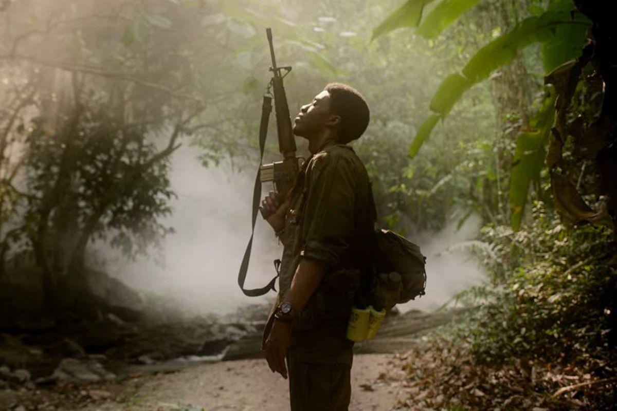 Da 5 Bloods: Chadwick Boseman holds his rifle