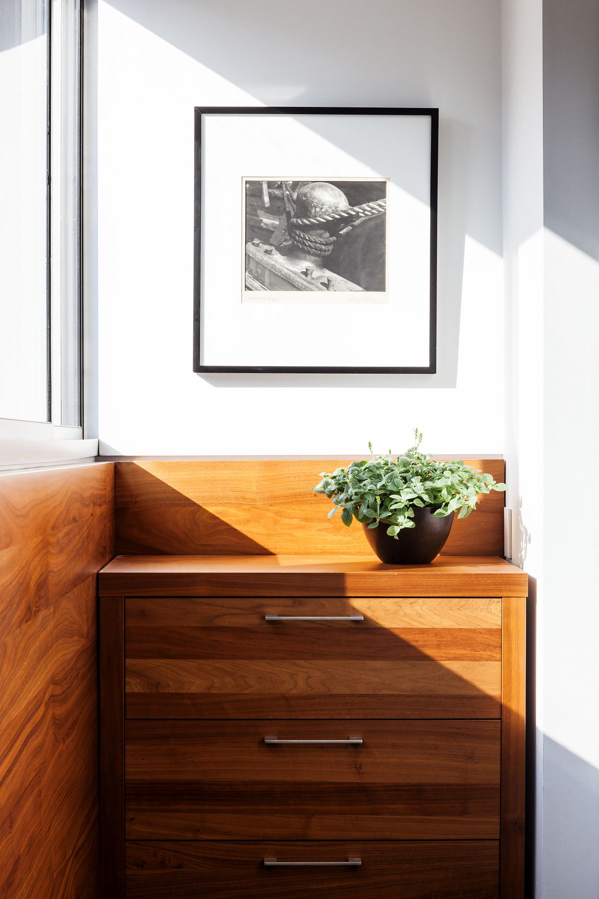 Detail of a room with wood wainscoting and a built-in dresser.