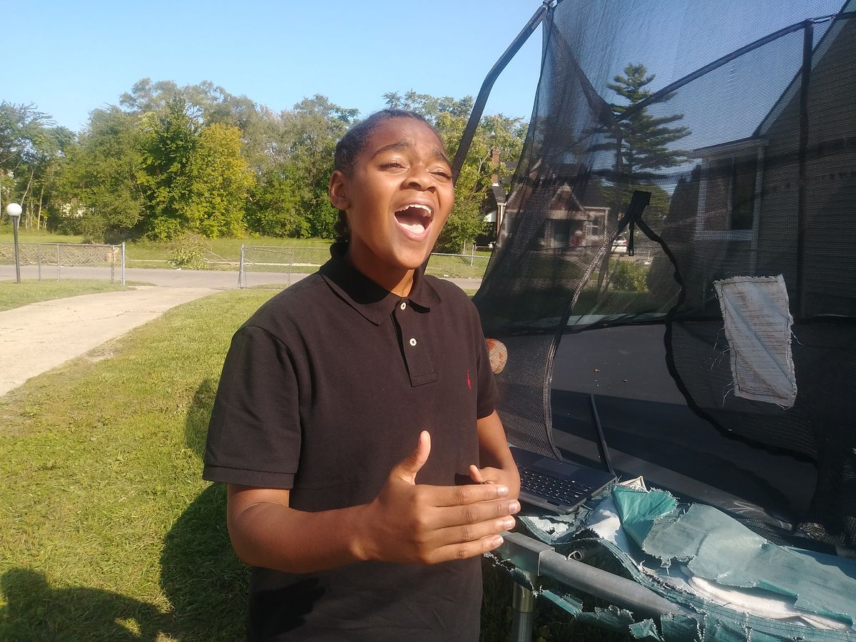 King Bethel singing outside on a sunny day.